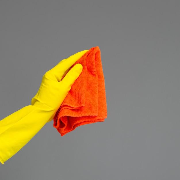 Uma mão em uma luva de borracha mantém um espanador de microfibra brilhante em um neutro. Foto Premium