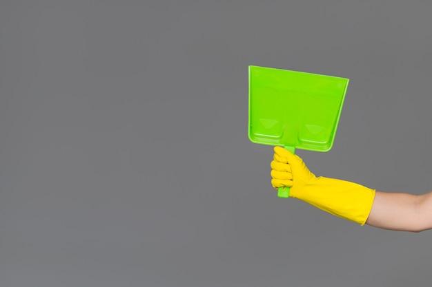 Uma mão em uma luva de borracha mantém uma colher em neutro Foto Premium