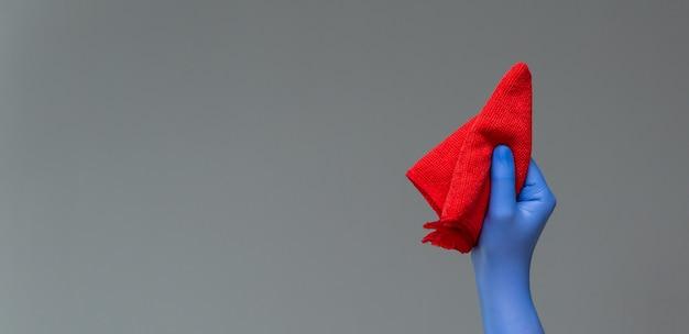 Uma mão em uma luva de borracha possui um espanador de microfibra brilhante Foto Premium