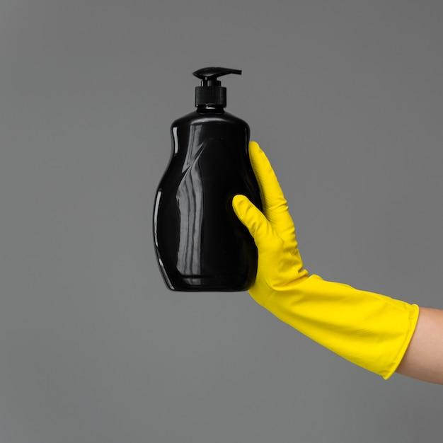 Uma mão em uma luva de borracha segura uma garrafa de detergente para lavar louça Foto Premium