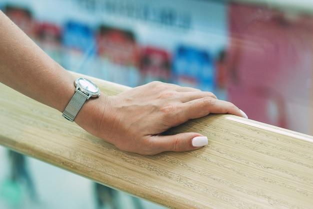 Uma mão feminina bonita segura o corrimão no shopping Foto Premium