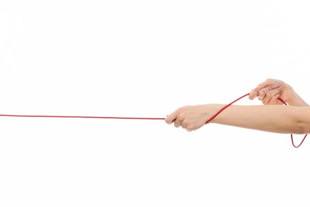 Uma mão feminina vista frontal, puxando a corda vermelha no branco Foto gratuita