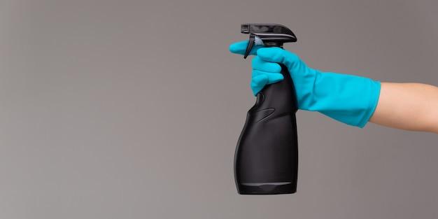 Uma mão na luva de borracha azul mantém o limpador de vidro em um frasco de spray Foto Premium