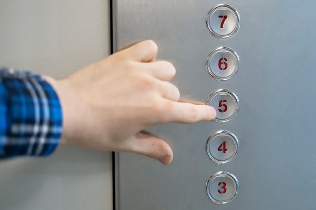Uma mão próxima apertando um botão na cabine do elevador Foto Premium