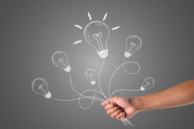 Uma mão que contém muitas idéias escritas com giz branco, desenha o conceito. Foto gratuita