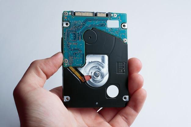 Uma mão segura a unidade de disco rígido contra o fundo branco Foto Premium