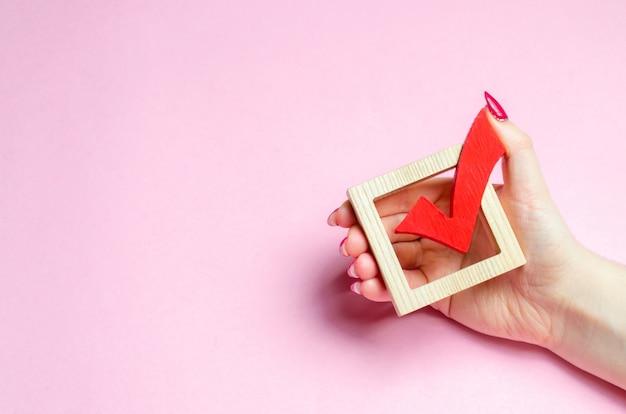 Uma mão segura um carrapato vermelho para votar Foto Premium