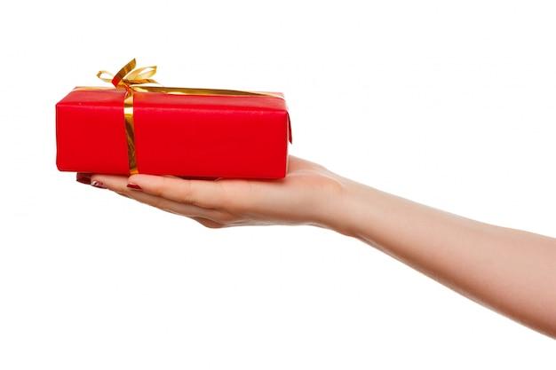 Uma mão segurando uma pequena caixa vermelha com uma fita na palma da mão, isolada no branco. Foto Premium