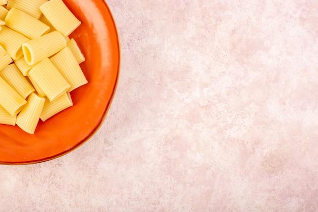 Uma massa italiana com vista de cima, saborosa e salgada em um prato redondo de laranja em uma mesa rosa Foto gratuita