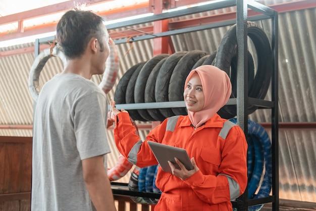 Uma mecânica asiática com véu usa um tablet digital enquanto conversa com consumidores do sexo masculino em pé com um suporte para pneus Foto Premium