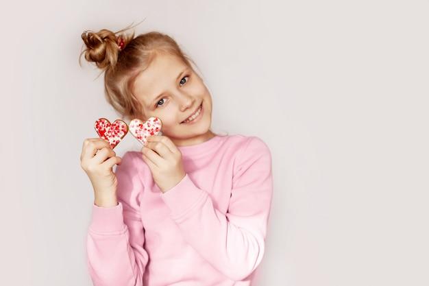 Uma menina alegre mantém pão de gengibre em forma de coração Foto Premium