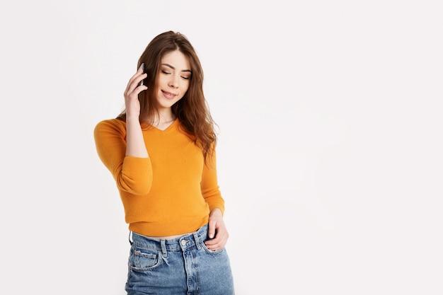 Uma menina alegre ri enquanto fala em um telefone móvel. uma morena está falando ao telefone sobre um fundo claro com espaço para texto Foto Premium