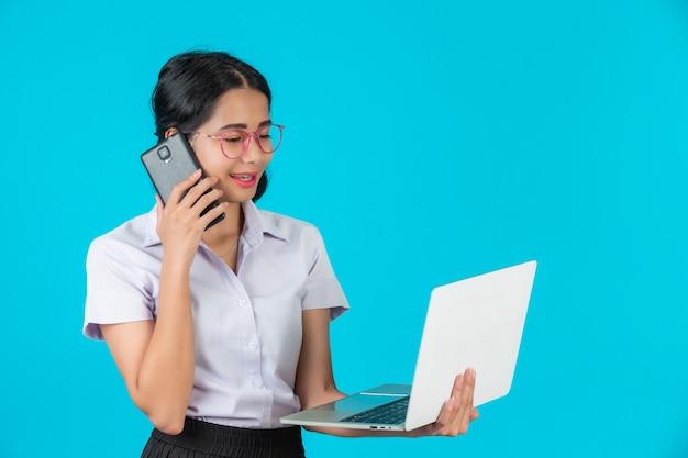 Uma menina asiática do estudante que guarda seu caderno em um azul. Foto gratuita