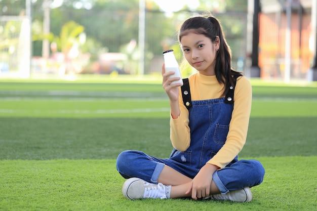 Uma menina asiática está bebendo uma deliciosa garrafa de leite. Foto Premium