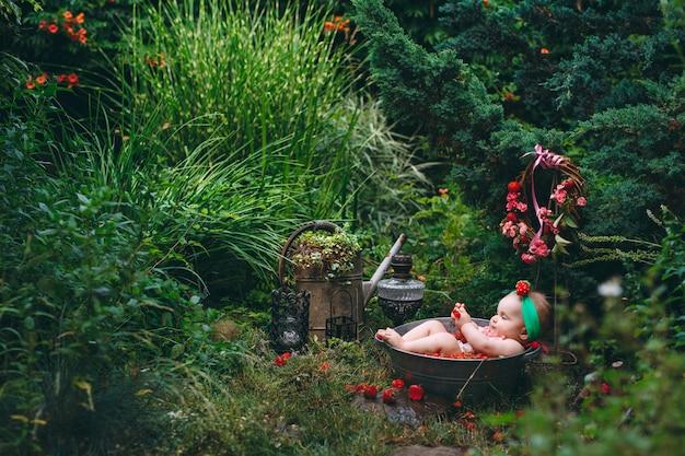 Uma menina banha-se em uma bacia com as morangos no jardim. Foto Premium