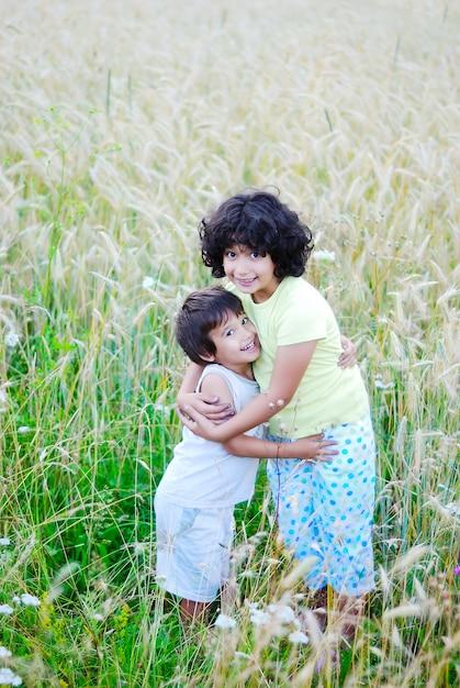 Uma menina bonita e um garoto no meio verde Foto Premium