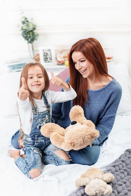 Uma menina bonitinha curtindo, brincando e criando com brinquedo com a mãe Foto gratuita