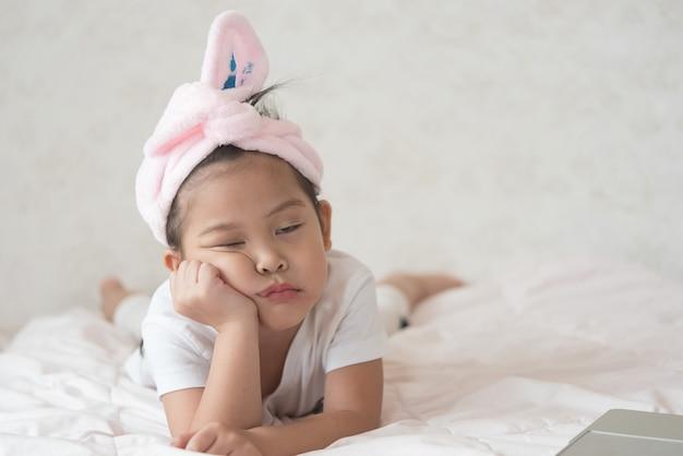 Uma menina bonitinha está fazendo uma carranca. ela não está feliz com alguma coisa. Foto Premium