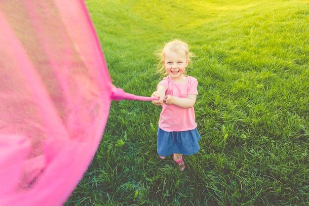 Uma menina bonito em uma saia de t-shirt e denim rosa corre ao redor do campo e pega borboletas. Foto Premium