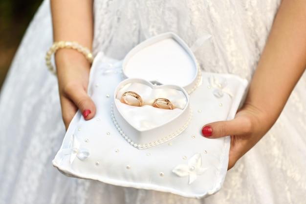 Uma menina carrega alianças de casamento em uma almofada em uma caixa em forma de coração Foto Premium