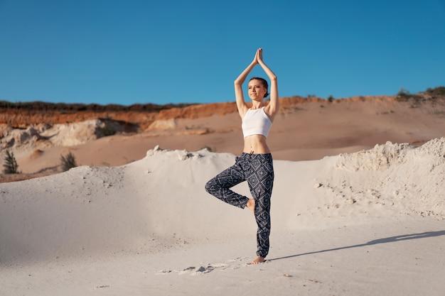 Uma menina caucasiano nova bonita em uma parte superior branca e em calças largas está em uma posição da árvore na praia na areia. com espaço para texto Foto Premium