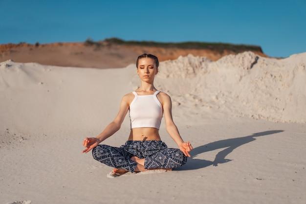 Uma menina caucasiano nova bonita em uma parte superior branca e em calças largas senta-se em uma posição de lótus na praia na areia. a pose mais popular para meditação. Foto Premium