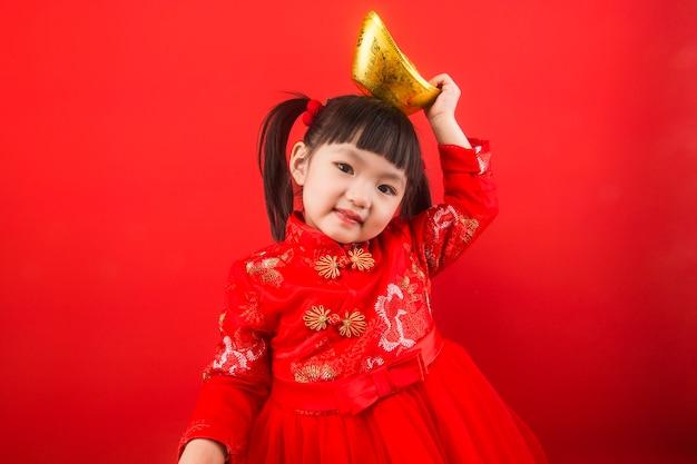 Uma menina chinesa celebra o festival da primavera com lingotes de ouro. tradução chinesa de lingotes de ouro: riqueza de lingotes de ouro Foto Premium