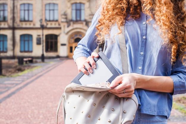 Uma menina com cabelo longo encaracolado tira um e-book de sua mochila Foto Premium