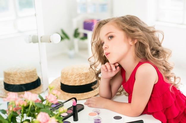 Uma menina com cosméticos, sentado perto do espelho. Foto gratuita