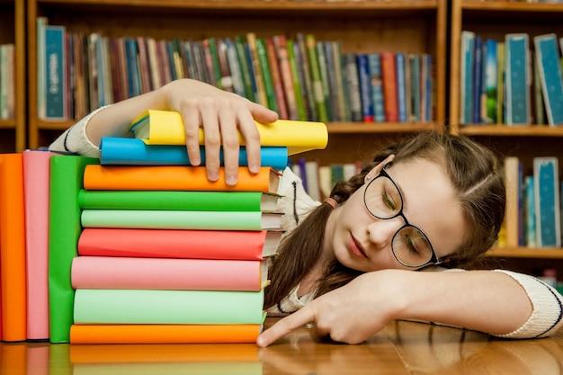 Uma menina com óculos quantos livros Foto Premium