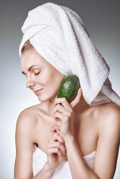 Uma menina com uma pele saudável e bonita segura um abacate perto do rosto Foto Premium