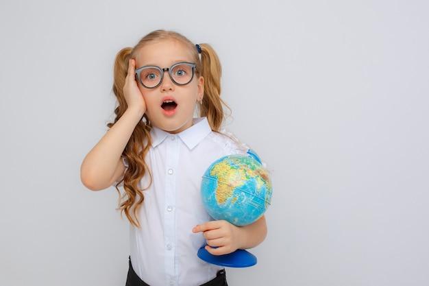 Uma menina com uniforme escolar e óculos segurando um globo nas mãos ajusta os óculos em um fundo branco Foto Premium