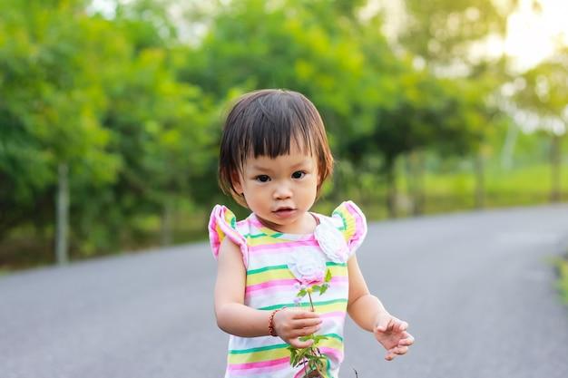 Uma menina de criança em pé e segurando uma grama floresce nas mãos no parque natural. Foto Premium