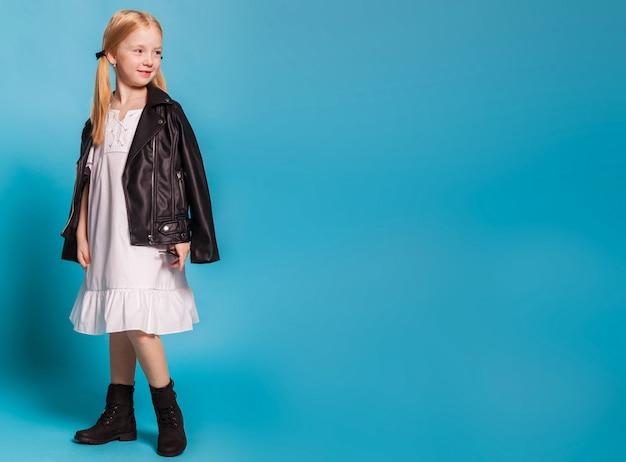 Uma menina de vestido branco e sapatos pretos Foto Premium
