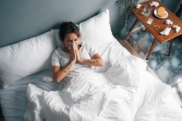 Uma menina doente assoa o nariz com lenços de papel na cama Foto Premium