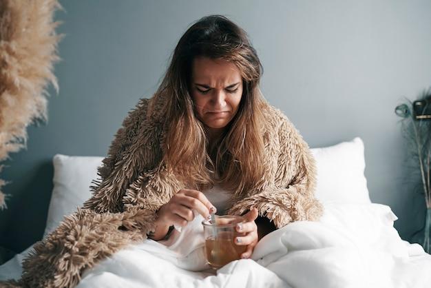 Uma menina doente com uma cara de nojo está bebendo seu remédio Foto Premium