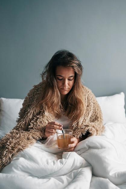 Uma menina doente na cama com um cobertor está bebendo chá quente Foto Premium