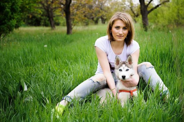 Uma menina e seu cão husky andando em um parque Foto Premium