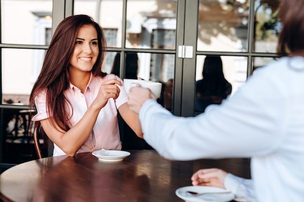 Uma menina e um jovem lade tilintando duas canecas de café em uma mesa de madeira em um café Foto Premium