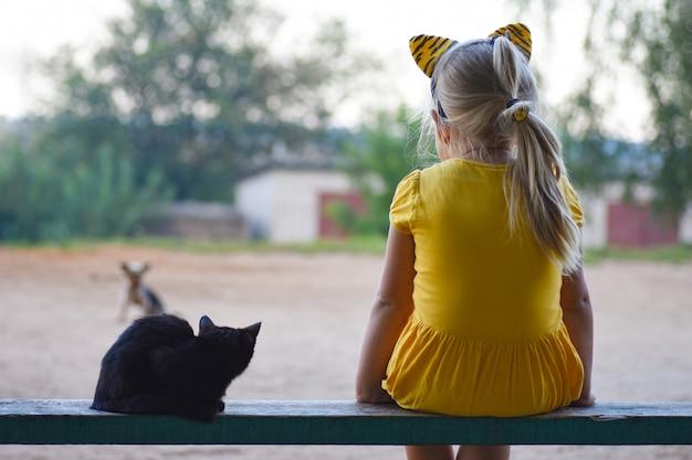 Uma menina em um vestido amarelo com um pequeno gato preto está sentado em um banco e olhando para um cachorro, vista traseira Foto Premium