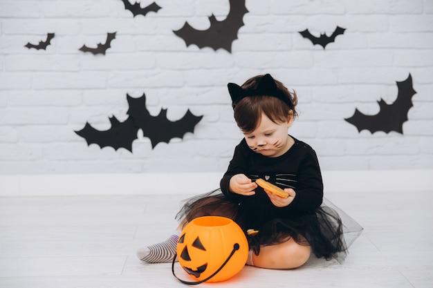 Uma menina em uma fantasia de gato preto com cesta de abóbora segurando um pão de gengibre Foto Premium