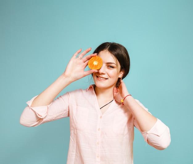 Uma menina feliz ri e esconde os olhos com fatias de tangerina em um fundo azul Foto Premium