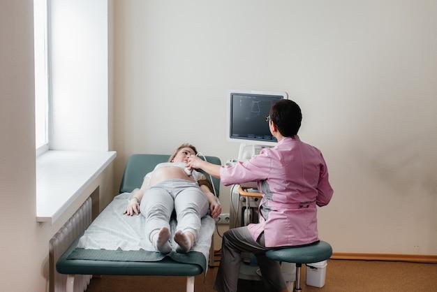 Uma menina grávida faz um ultrassom de seu abdômen na clínica Foto Premium