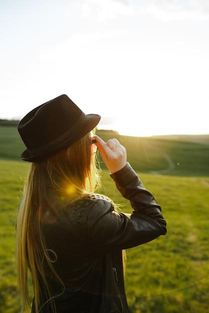 Uma menina loira olhando o pôr do sol na primavera Foto Premium