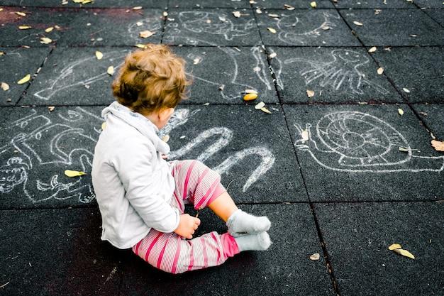 Uma menina olha os desenhos de giz no chão de um playground. Foto Premium
