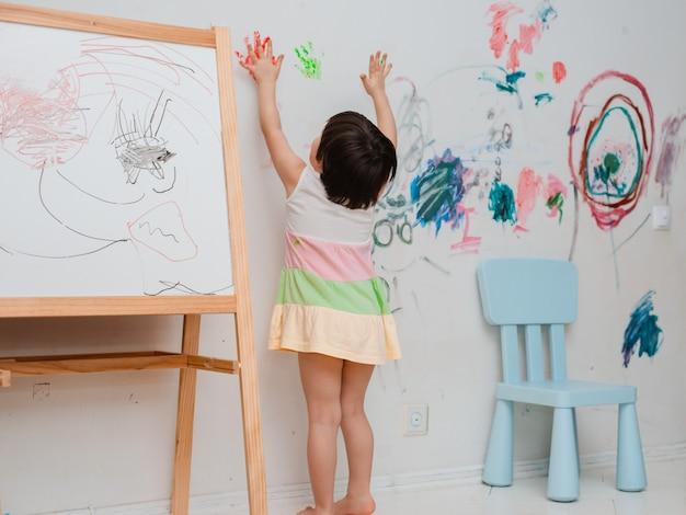 Uma menina pintou um olhar arqueado com tinta e um pincel na parede do quarto dela. Foto Premium