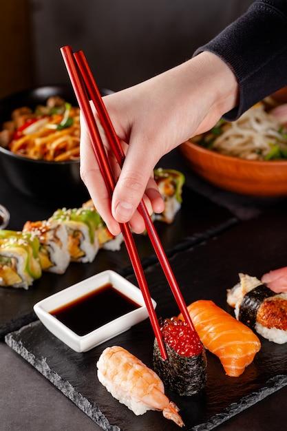 Uma menina prende os pauzinhos chineses vermelhos e come o sushi em um restaurante. Foto Premium