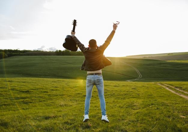 Uma menina pulando de alegria ao pôr do sol Foto Premium