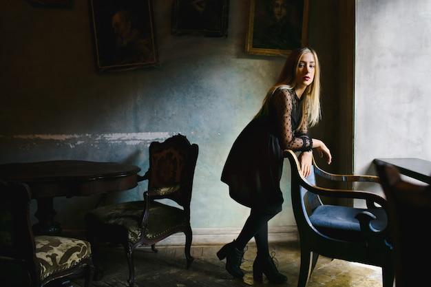 Uma menina se inclina em uma cadeira vintage no café Foto gratuita