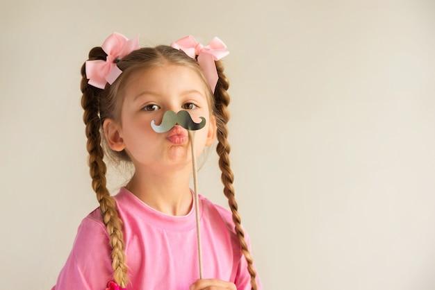 Uma menina segurando um bigode chique. Foto Premium